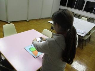 アイデア 写真 デジカメで児童の作品を撮影している様子